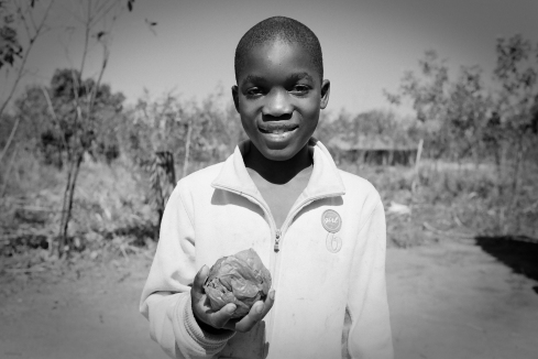 A young boy in Mozambique shows off his plastic bag ball.