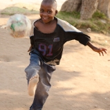 "Child at Musha Wevana children's home in Marondera, Zimbabwe, kicking one of their old ""soccer balls"" made from plastic bags."