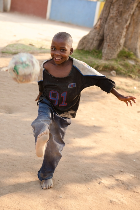 """Child at Musha Wevana children's home in Marondera, Zimbabwe, kicking one of their old """"soccer balls"""" made from plastic bags."""